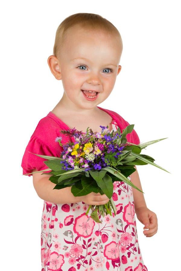 Mooi babymeisje met een ruikertje van bloemen royalty-vrije stock afbeelding
