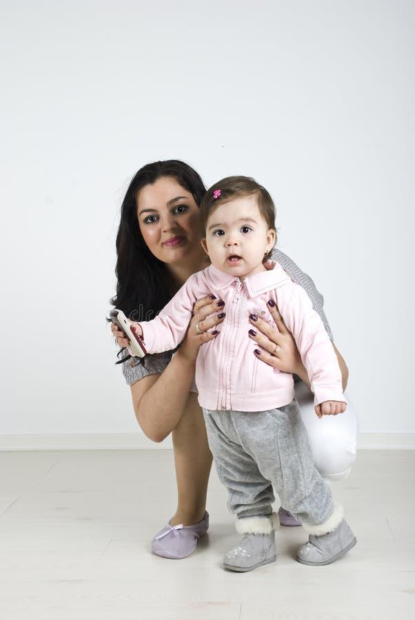 Mooi babymeisje met haar moeder stock afbeelding