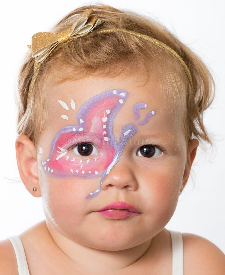 Mooi babymeisje met schilderijen op haar gezicht van een vlinder stock afbeeldingen