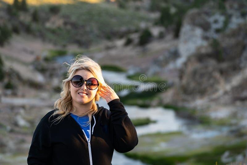 Mooi backlit portret van een blondevrouw die toevallige kleding, vingers in haar blondehaar dragen Genomen bij Hete Kreek Mammoet stock foto