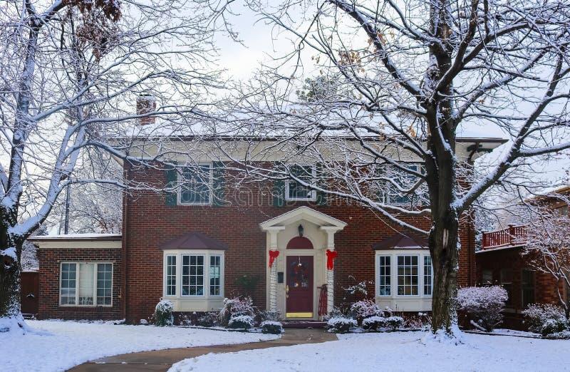 Mooi baksteenhuis met erkers met Kerstboom door en verfraaide pijlers en slee die op portiek in ontworpen sneeuw tonen royalty-vrije stock afbeeldingen