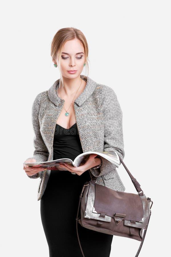 mooi bedrijfsvrouwenblonde die in zwarte kleding, jasje een tijdschrift op grijze achtergrond lezen royalty-vrije stock foto