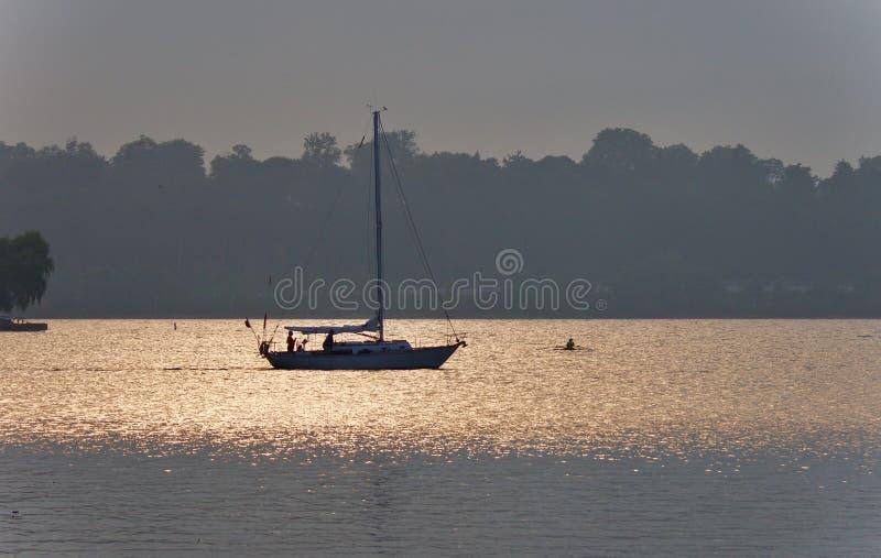 Mooi beeld van een meer en een boot op zonsondergang stock foto's