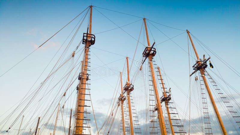 Mooi beeld van hoge mast van historische houten schepen en boten tegen blauwe hemel stock foto