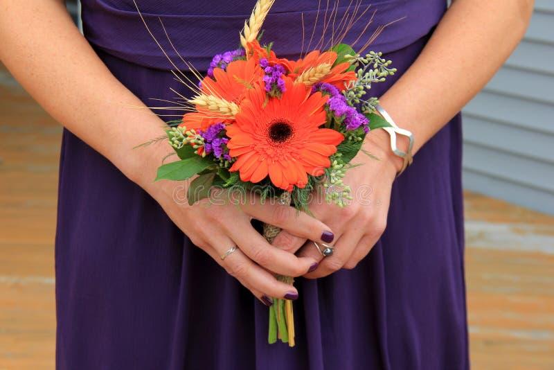 Mooi beeld van jonge vrouw in de purpere bloemen van de kledingsholding royalty-vrije stock afbeelding