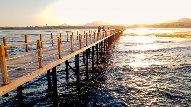Mooi beeld van lange houten pijler in ea Verbazende zonsondergang over de brug in oceaan stock fotografie