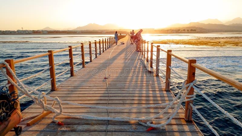 Mooi beeld van lange houten pijler in ea Verbazende zonsondergang over de brug in oceaan royalty-vrije stock afbeelding