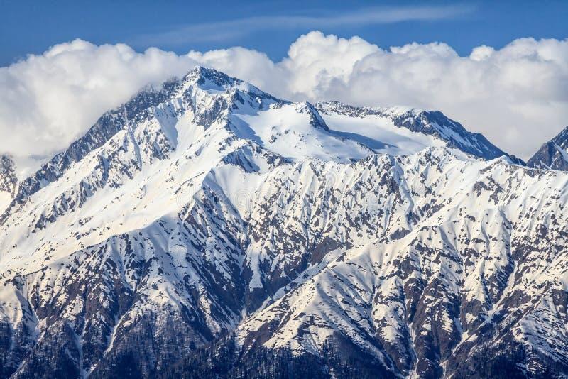 Mooi berglandschap van de Belangrijkste Kaukasische rand met sneeuwpiek op blauwe bewolkte hemelachtergrond stock afbeelding