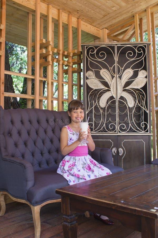 Mooi betoverend meisje in kleurrijke kledingszitting in leunstoel royalty-vrije stock fotografie