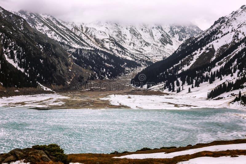 Mooi bevroren meer in de bergen met snow-capped pieken royalty-vrije stock foto