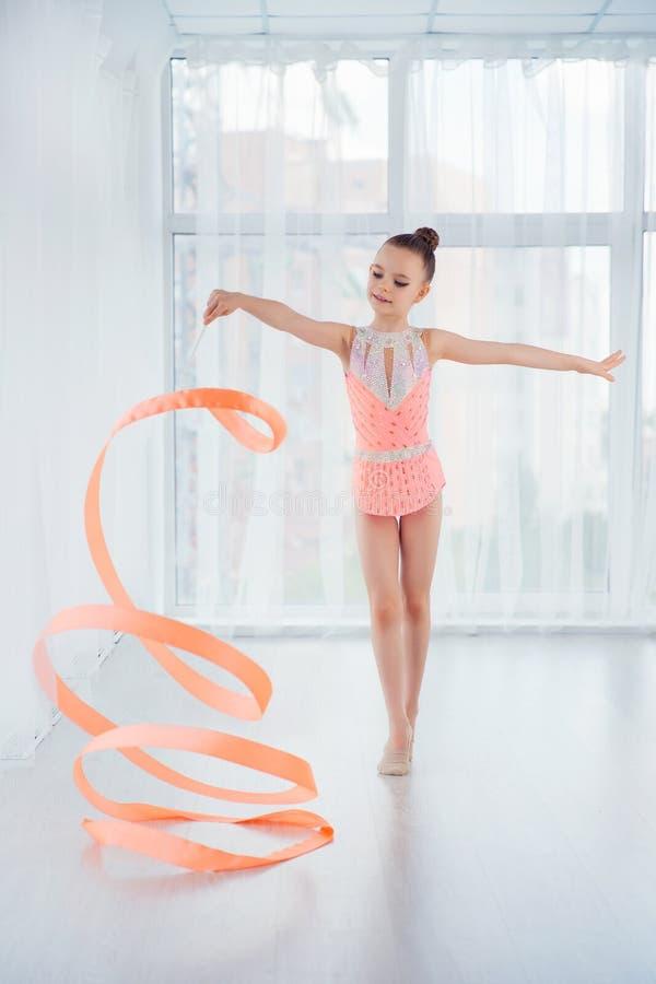 Mooi beweegt weinig turnermeisje in roze sportkledingskleding, die ritmische gymnastiekoefening doen met kunstlint spiraalsgewijs stock foto
