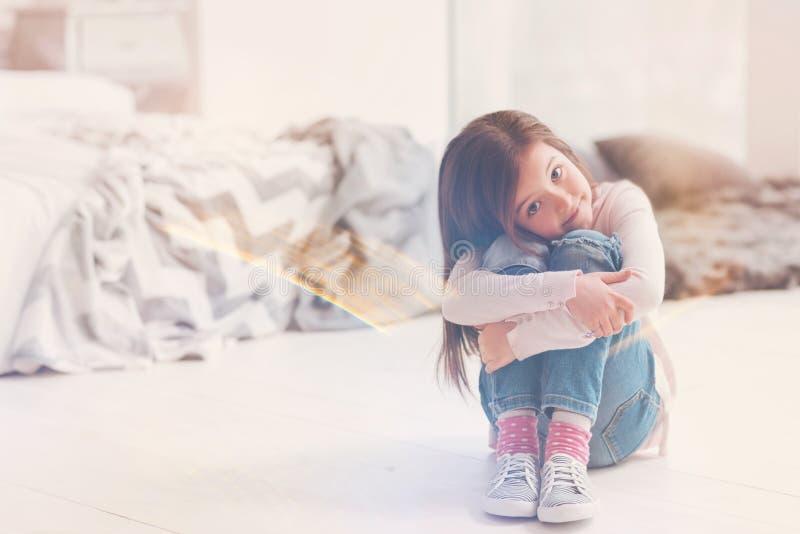 Mooi bewonderenswaardig kind die haar knieën koesteren royalty-vrije stock fotografie