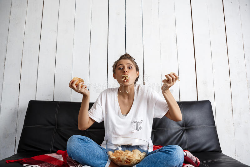 Mooi binnenlands meisje die spaanders eten, lettend op TV, die bij bank zitten stock fotografie