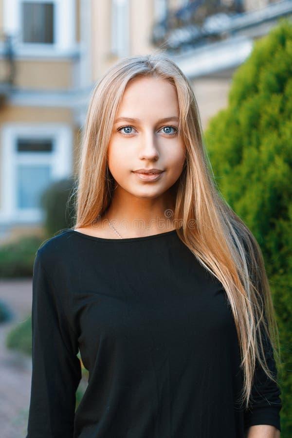 Mooi blauw-eyed meisje op de achtergrond van huizen stock foto's