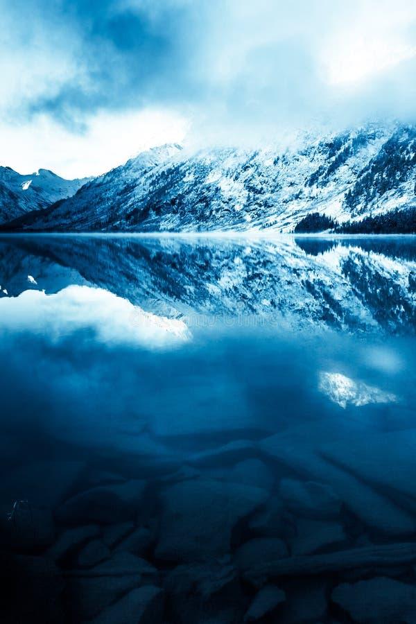 Mooi blauw meer in de bergen Vlakke spiegeloppervlakte van het water onder de wolken De schoonheid van de winteraard royalty-vrije stock foto