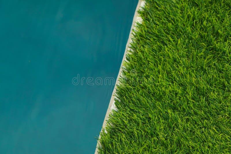Mooi Blauw Water en Kunstmatig gras groen gras behang stock fotografie