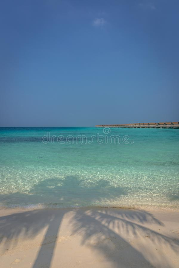 Mooi blauw waterstrand in een tropisch paradijs, met bungalowwen op de achtergrond in de Maldiven stock fotografie
