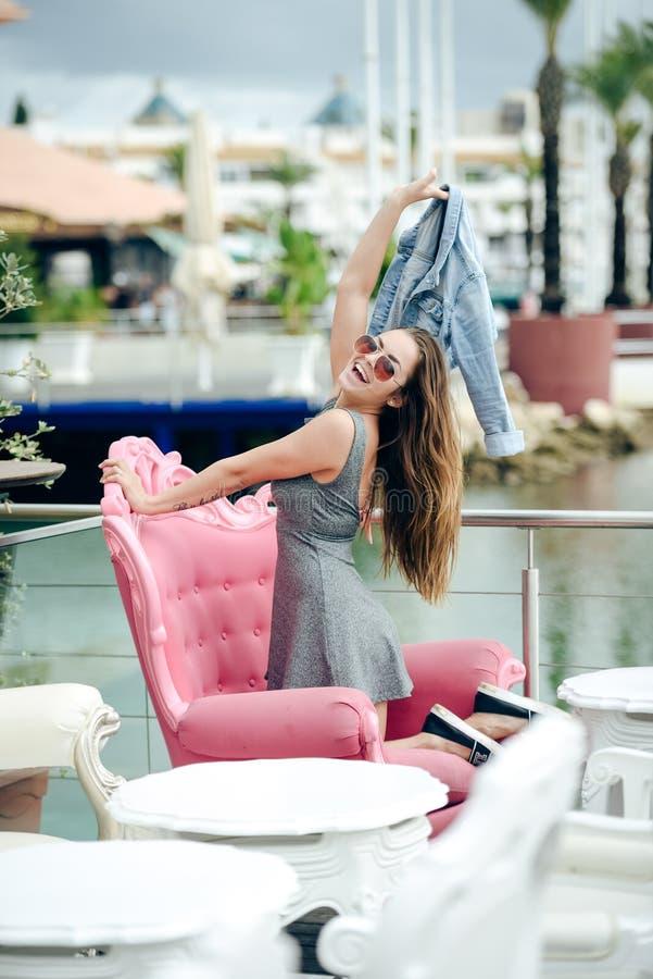 Mooi blij gelukkig glimlachend mooi wijfje in restaurant op de achtergrond van de luxejachthaven stock afbeelding