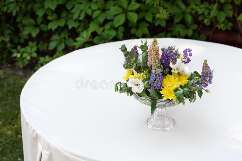 Mooi bloemboeket in openlucht Huwelijks floristische decoratie bij witte lijst royalty-vrije stock foto's
