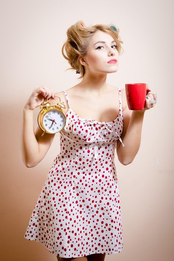 Mooi blond grappig pinupmeisje die met krulspelden gouden alarm-klok & kop van hete drank houden die cameraportret bekijken stock afbeelding