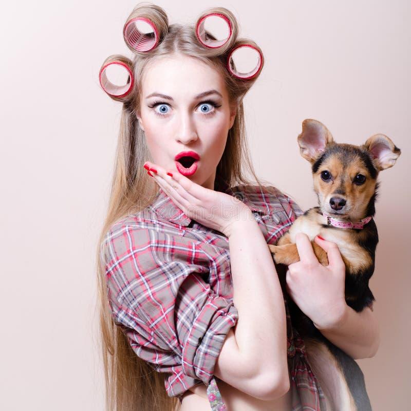 Mooi blond jong blauw de ogenmeisje die van de pinupvrouw pret het spelen met leuke kleine hond hebben die camera bekijken stock foto's