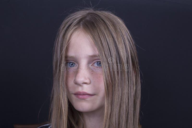 Mooi blond jong meisje met sproeten binnen op zwarte achtergrond, close-upportret royalty-vrije stock afbeeldingen