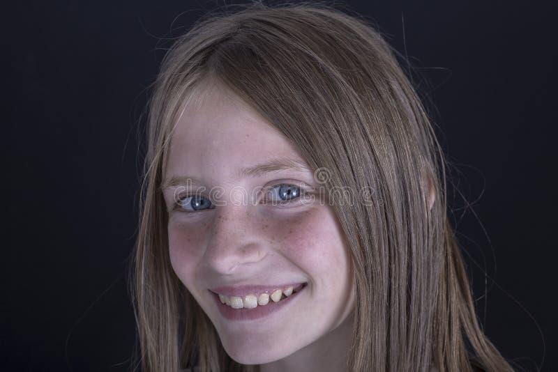 Mooi blond jong meisje met sproeten binnen op zwarte achtergrond, close-upportret royalty-vrije stock foto's