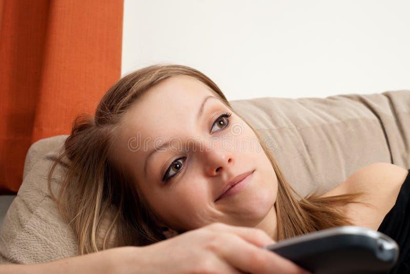 Mooi blond meisje dat op TV let stock foto's
