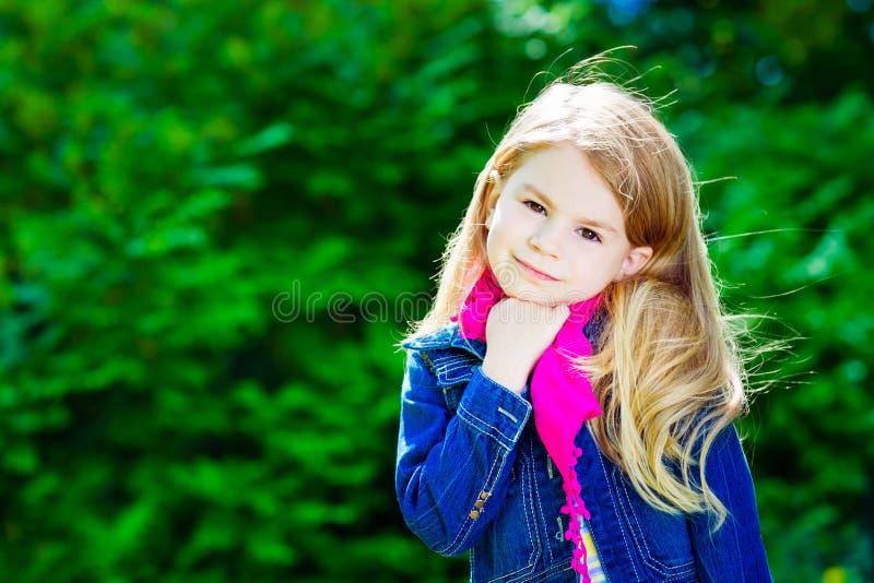 Mooi blond meisje die roze sjaal dragen stock afbeelding