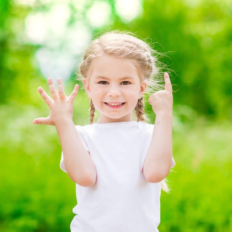 Mooi blond meisje die zes vingers (haar tijd) tonen  stock afbeelding