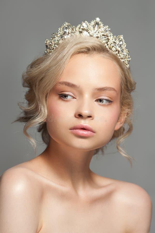 Mooi blond meisje in het beeld van een bruid met een tiara in haar haar royalty-vrije stock foto's