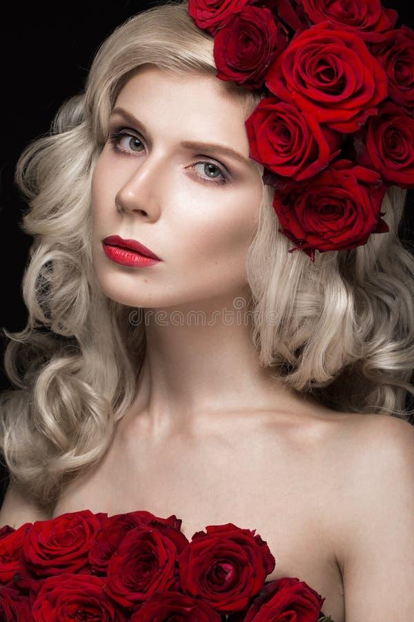 Mooi blond meisje in kleding en hoed met rozen, klassieke make-up, krullen, rode lippen Het Gezicht van de schoonheid stock fotografie