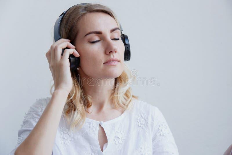 Mooi blond meisje met hoofdtelefoons op een lichte achtergrond Zij geniet van luister aan muziek en hebbend pret stock foto's