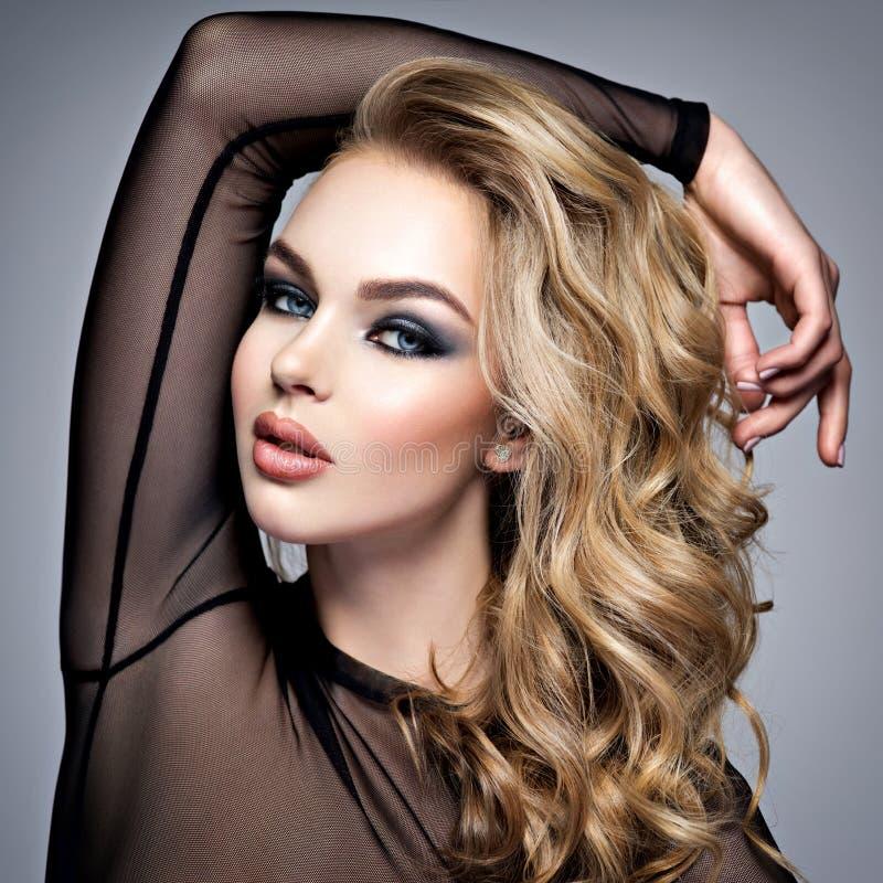 Mooi blond meisje met make-up rokerige ogen stock foto