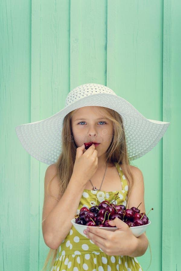 Mooi blond meisje op een achtergrond van turkooise muur in de witte plaat van de hoedenholding met kers royalty-vrije stock afbeelding