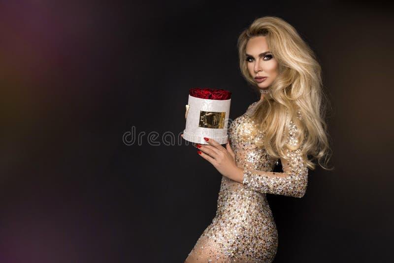 Mooi blond model die in elegante kleding een gift, bloemdoos met rozen houden De gift van de valentijnskaart `s stock foto's