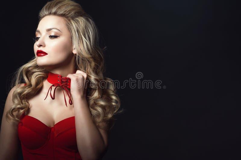 Mooi blond model die rode korset vastgebonden bovenkant dragen die verbonden nauwsluitende halsketting proberen op te stijgen om  royalty-vrije stock fotografie