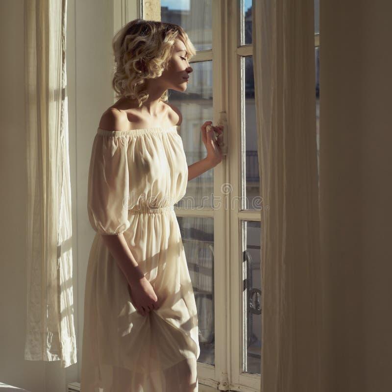 Mooi blonde bij het venster stock fotografie