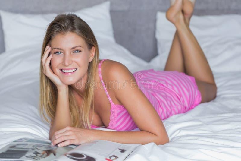 Mooi blonde die op haar tijdschrift liggen die van de bedlezing bij ca glimlachen stock foto
