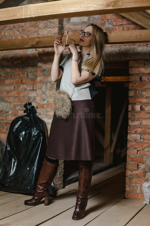 Mooi blonde in glazen en laarzen die zich in zolder bevinden stock afbeeldingen