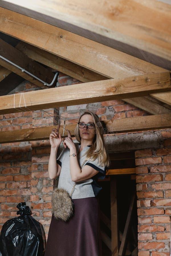 Mooi blonde in glazen en laarzen die zich in zolder bevinden stock afbeelding