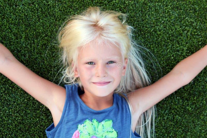 Mooi blonde glimlachend meisje die op het gras op een de zomerdag liggen royalty-vrije stock foto