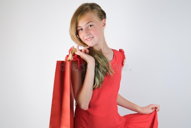 Mooi blonde Kaukasisch meisje die in rode kleding een document zak in haar hand houden royalty-vrije stock foto