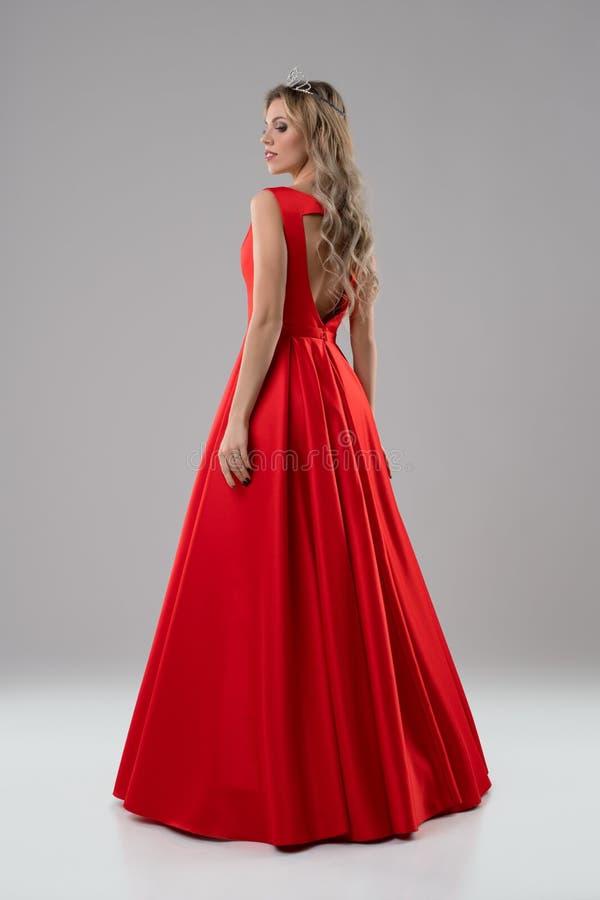 Mooi blonde in luxueus rood avondjurkschot stock afbeeldingen