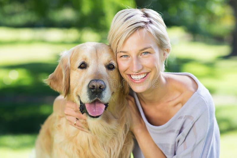 Mooi blonde met haar hond in het park royalty-vrije stock foto