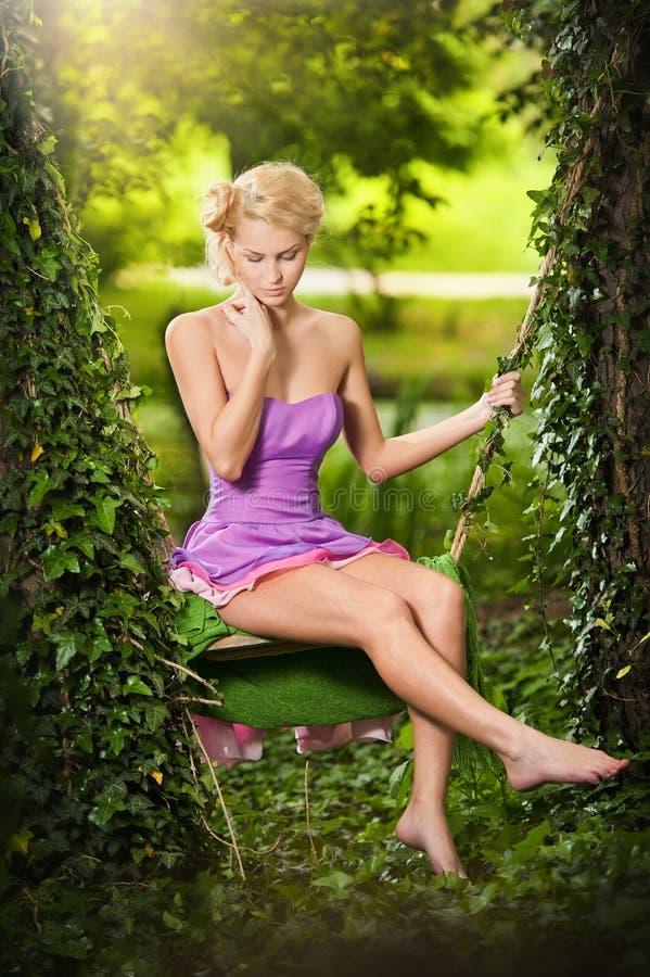 Mooi blonde met korte kleding en creatief kapsel in tuinschommeling royalty-vrije stock afbeelding