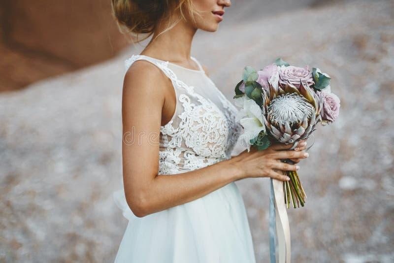 Mooi blonde modelmeisje met de modellering van huwelijkskapsel in een modieuze witte kantkleding met een boeket van exotics royalty-vrije stock fotografie