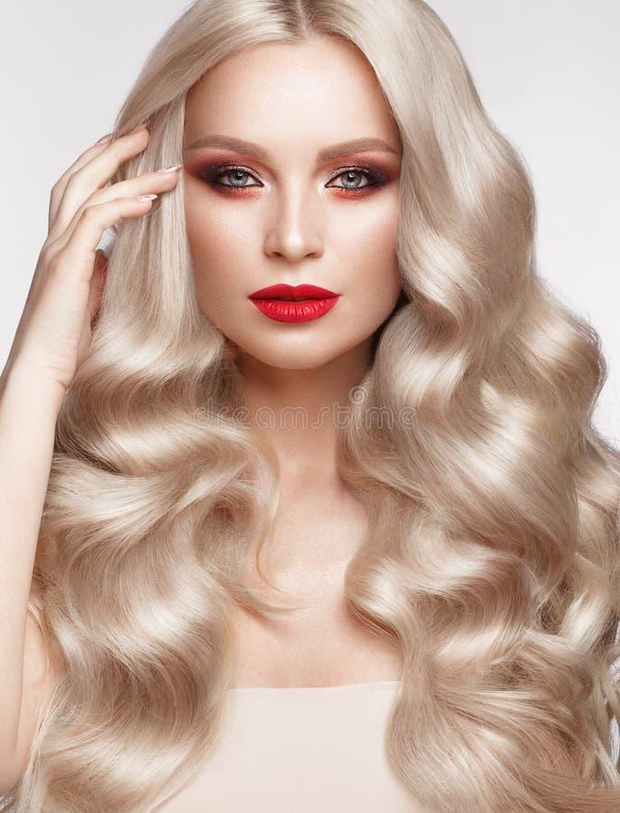 Mooi blonde op een Hollywood-manier met krullen, natuurlijke make-up en rode lippen Het gezicht en het haar van de schoonheid stock afbeelding