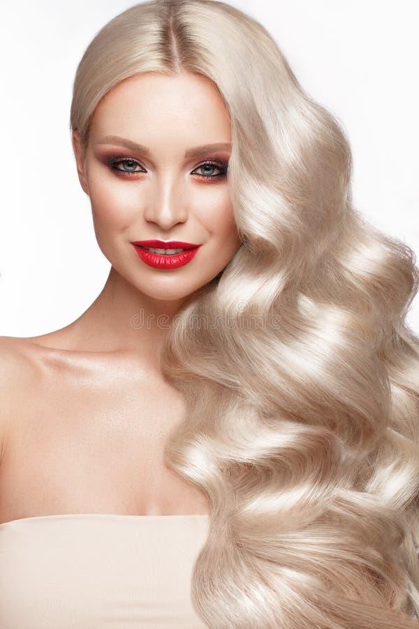 Mooi blonde op een Hollywood-manier met krullen, natuurlijke make-up en rode lippen Het gezicht en het haar van de schoonheid royalty-vrije stock fotografie