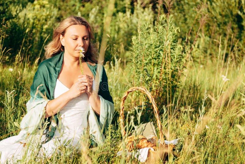 Mooi blonde op kamillegebied, leuke vrouwelijke het genieten van geur van Daisy royalty-vrije stock foto's